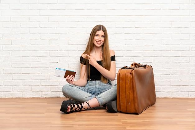 Mujer viajera con maleta y tarjeta de embarque apuntando hacia un lado para presentar un producto