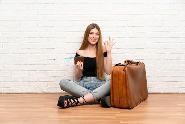 Mujer viajera con maleta y tarjeta de embarque que muestra el signo correcto con los dedos