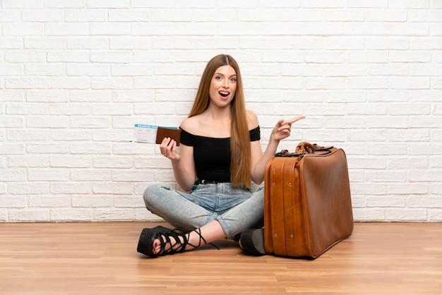 Mujer viajera con maleta y tarjeta de embarque sorprendida y apuntando con el dedo a un lado
