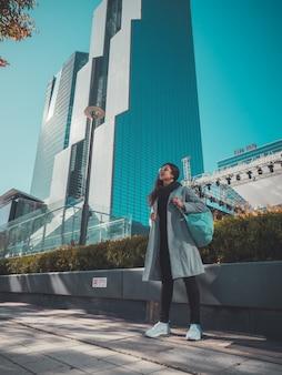 Mujer viajera en seúl cerca de rascacielos. vista de otoño