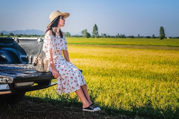 Mujer viajera tiene un tiempo de relax durante el viaje al lado de la carretera.