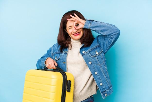 Mujer de viajero latino de edad middlr sosteniendo una maleta aislado emocionado manteniendo el gesto ok en el ojo.