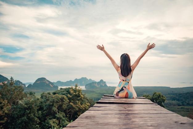 Mujer de viajero de libertad relajante con los brazos levantados en la cima de la montaña.