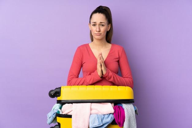 Mujer viajero con una maleta llena de ropa sobre pared púrpura aislada suplicando