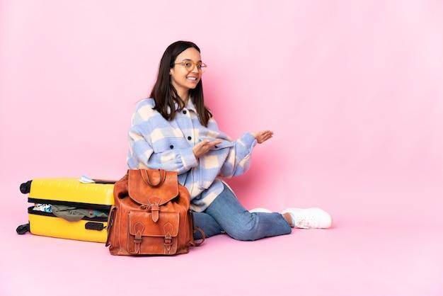 Mujer viajero con una maleta sentada en el suelo extendiendo las manos hacia el lado para invitar a venir