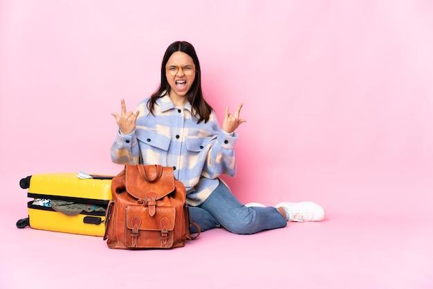 Mujer viajero con una maleta sentada en el suelo haciendo gesto de bocina