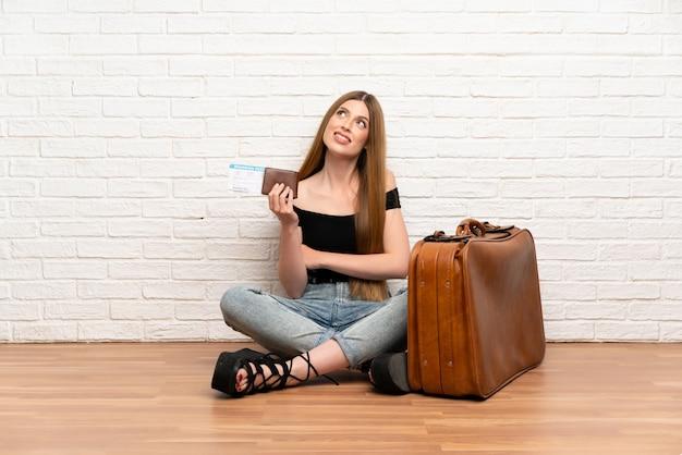 Mujer del viajero con maleta y tarjeta de embarque mirando hacia arriba mientras sonríe