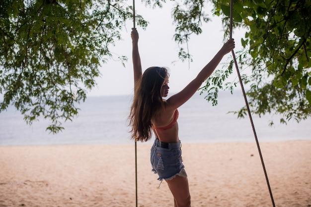 Mujer viajero relajante en columpio de madera en la playa