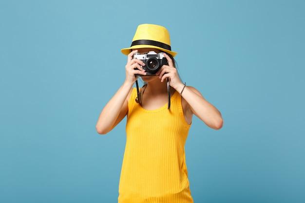 Mujer viajero en ropa casual de verano amarillo y sombrero con cámara de fotos en azul