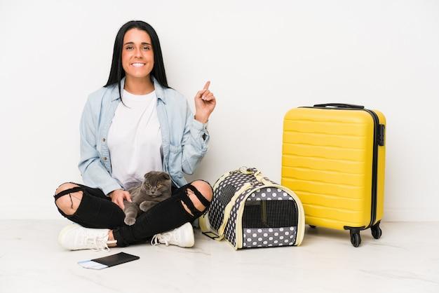 Mujer viajero con su gato aislado en la pared blanca sonriendo y apuntando a un lado, mostrando algo en el espacio en blanco.