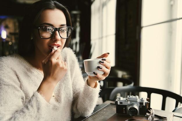 La mujer en vidrios bebe el café y come el azúcar en la tabla en café brillante