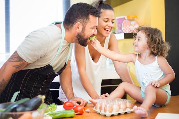 Mujer viendo hija alimentando pimiento a su padre