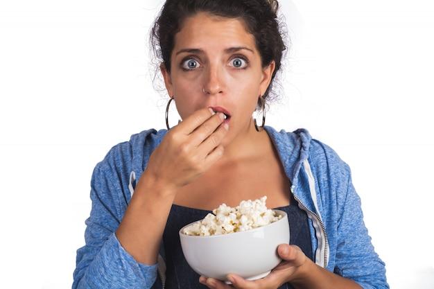 Mujer viendo una película mientras come palomitas de maíz.