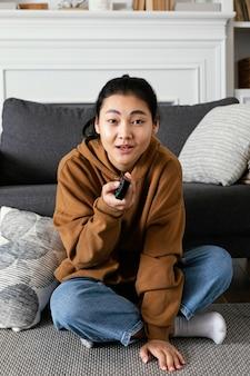 Mujer viendo la televisión y sosteniendo el control remoto