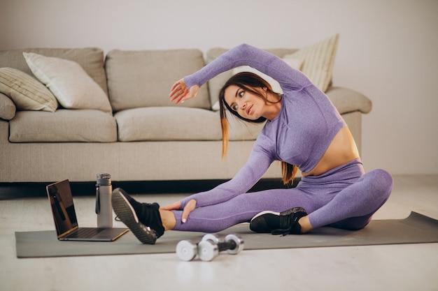 Mujer viendo tutoriales y entrenamientos desde casa en tapete usando comba y mancuernas