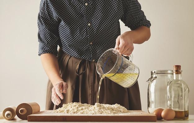 La mujer vierte agua con aceite de oliva de la taza medidora a la harina a bordo, para preparar la masa para pastas o bolas de masa. presentación de la guía de cocina