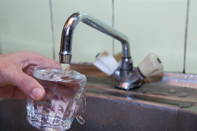 La mujer vierte agua de la grúa en un vaso.