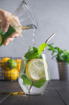 Mujer vierte agua infundida con limón, jengibre y menta en vaso. de cerca. bebida de desintoxicación saludable.