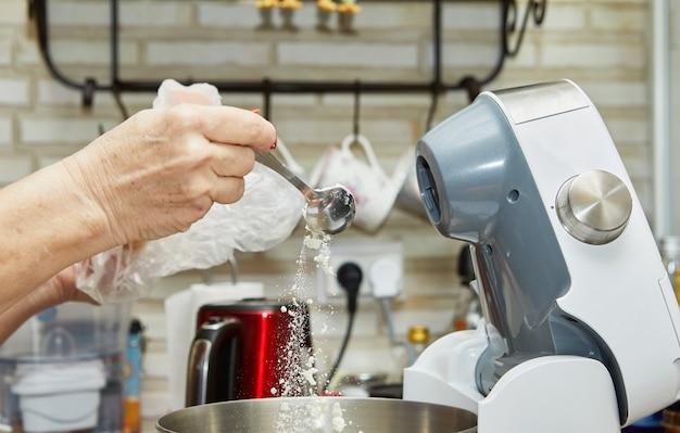 La mujer vierte harina en el tazón de la batidora para hacer muffins de tomate secados al sol.