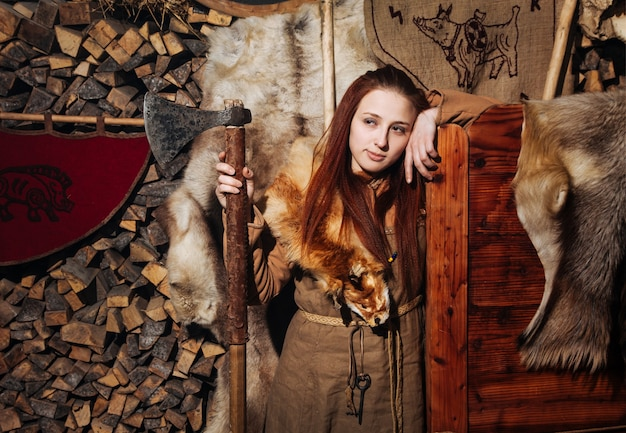 Mujer vikinga posando contra el antiguo interior de los vikingos.