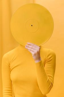 Mujer con vinilo enfrente de la cara en escenario amarillo