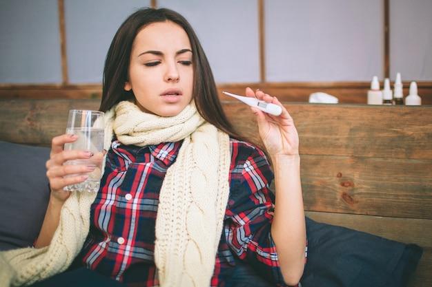 Mujer con virus de la gripe acostada en la cama, mide su temperatura con un termómetro y se toca la frente.