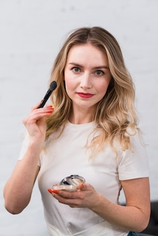 Mujer visagiste posando para cámara con cosméticos.