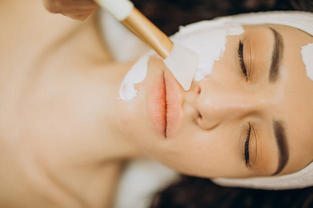 Mujer visitando cosmetóloga y realizando procedimientos de rejuvenecimiento.