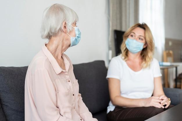 Mujer visitando a su pariente en el hogar de ancianos y vistiendo máscara médica