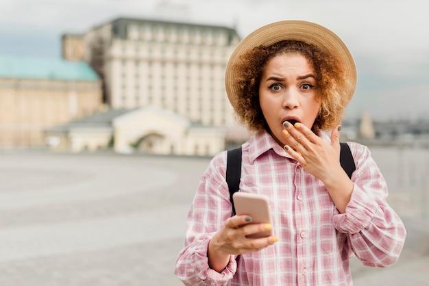 Mujer de vista frontal comprobando su teléfono mientras viaja