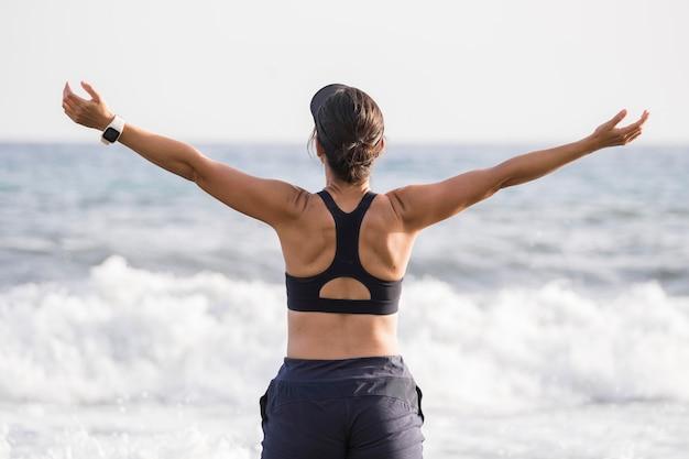 Mujer de vista frontal disfrutando de la playa después de correr