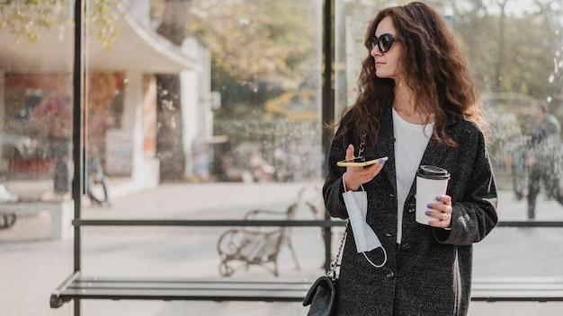 Mujer de vista frontal esperando en la estación de autobuses