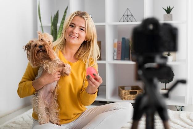 Mujer de vista frontal grabando video con su mascota