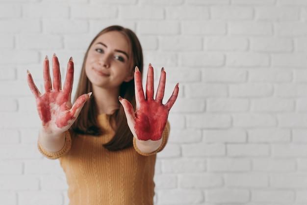 Mujer de vista frontal con manos pintadas
