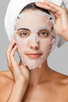 Mujer de vista frontal con máscara de belleza facial