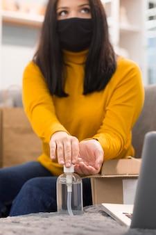 Mujer de vista frontal con máscara médica desinfectando sus manos