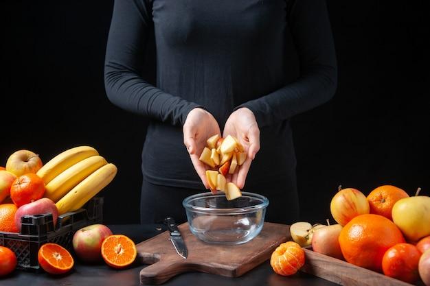 Mujer de vista frontal poniendo rodajas de manzana fresca en un tazón de frutas en bandeja de madera en la mesa