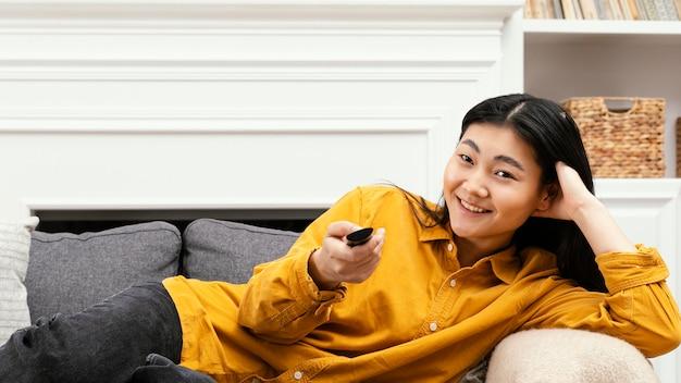 Mujer de vista frontal sentada en el sofá y viendo la televisión