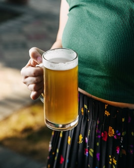 Una mujer de vista frontal sosteniendo cerveza hielo y frío fuera de bebida alcohólica