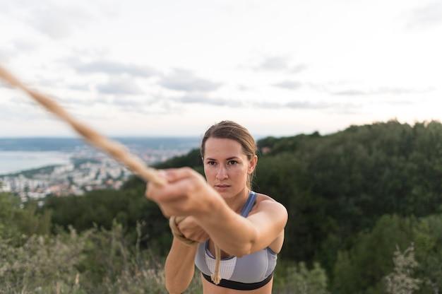 Mujer de vista frontal sosteniendo una cuerda dura