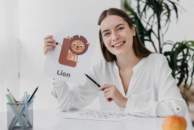 Mujer de vista frontal sosteniendo una ilustración de león