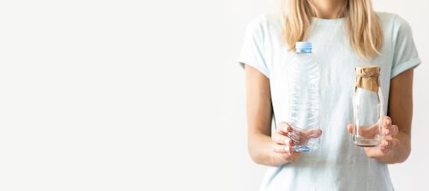 Mujer de vista frontal sosteniendo vasos de plástico con espacio de copia