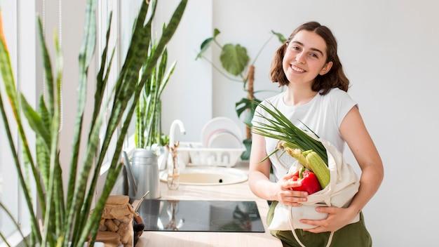 Mujer de vista frontal sosteniendo verduras orgánicas