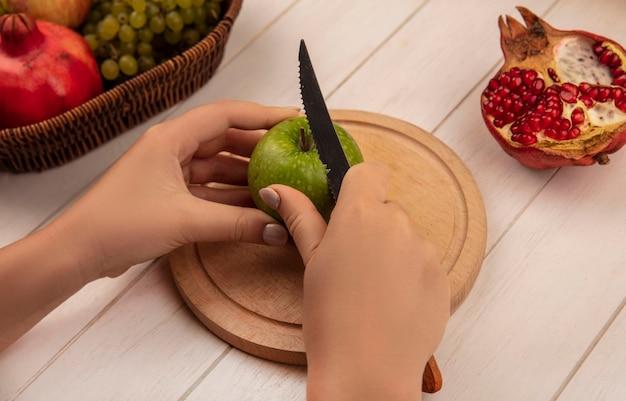 Mujer de vista lateral corta manzana verde sobre una tabla de cortar con granadas en una pared blanca