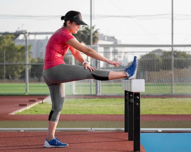 Mujer de vista lateral entrenando antes de correr