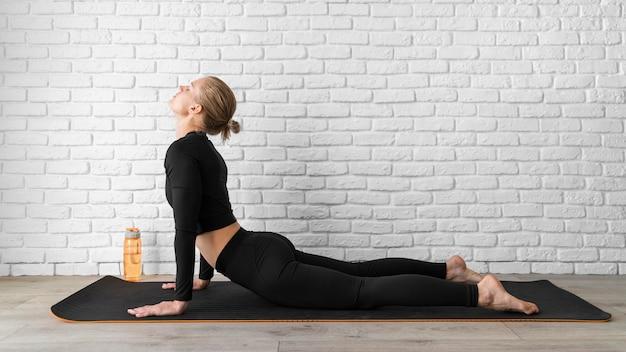 Mujer de vista lateral estirando su espalda