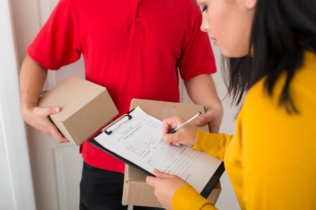Mujer de vista lateral firmando un papel de entrega
