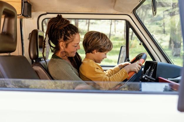 Mujer de vista lateral con hijo en su regazo conduciendo