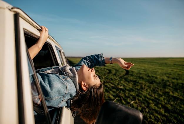 Mujer de vista lateral quedarse con la cabeza fuera de una camioneta