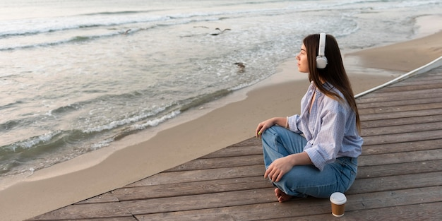 Mujer de vista lateral sentada junto a la playa con espacio de copia